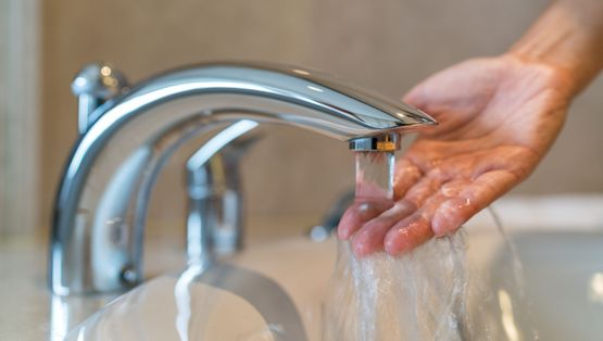 Hand washing in hot water from bathroom faucet